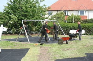 Safety Surface being installed under toddler swings
